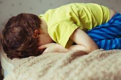 说谎在与下来他的面孔的床上的疲乏的小孩男孩 哭泣的小孩 免版税库存照片