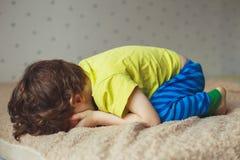 说谎在与下来他的面孔的床上的疲乏的小孩男孩 哭泣的小孩 库存照片