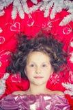 说谎在与圣诞节诗歌选的一个红色地板和冷杉分支上的一个小金发女孩在她的头附近 免版税库存图片
