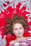 说谎在与圣诞节诗歌选的一个红色地板和冷杉分支上的一个小金发女孩在她的头附近 免版税图库摄影