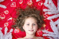 说谎在与圣诞节诗歌选的一个红色地板和冷杉分支上的一个小金发女孩在她的头附近 图库摄影