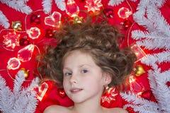 说谎在与圣诞节诗歌选的一个红色地板和冷杉分支上的一个小金发女孩在她的头附近 免版税库存照片