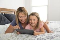 说谎在与她的年轻甜点的床上的年轻白肤金发的白种人母亲7岁使用数字式互联网片剂垫的女儿互联网 免版税库存图片