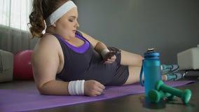说谎在与智能手机的地板上的肥胖懒惰妇女在手上而不是训练 影视素材