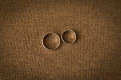 说谎在与橙色和米黄玫瑰的婚礼花束的两个婚姻的金黄圆环 免版税库存照片