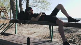 说谎在与水bidon瓶的长凳的坚强的运动专业骑自行车者在地面上 享用的骑自行车者平衡太阳 股票录像