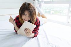 说谎在与片剂计算机的床上的愉快的年轻女人 免版税库存照片