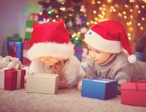 说谎在与礼物的地板上的男孩和女孩临近圣诞树 免版税库存照片