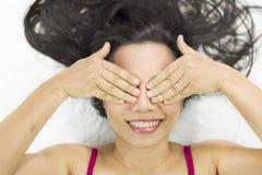 说谎在与黑长发的地面的亚裔妇女 代理微笑,愉快和显示紧密她的眼睛 免版税库存图片