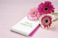 说谎在书写纸,粉红彩笔colore的三朵大丁草花 免版税库存照片