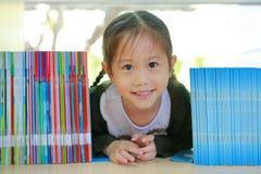 说谎在书架的愉快的矮小的亚裔儿童女孩在图书馆 儿童创造性和想象力概念 免版税图库摄影