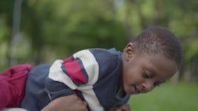 说谎在他的母亲顶部的小非裔美国人的男孩特写镜头  使用与孩子的妇女,拉扯他的鼻子 股票录像
