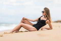 说谎在佩带时髦的游泳衣的海滩的沙子的性少女作为sunbath enjoying holidays summer 免版税库存照片