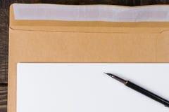 说谎在信封的白纸板料 钢笔是 图库摄影