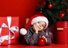 说谎在圣诞树背景的圣诞老人红色帽子的滑稽的微笑的孩子 免版税库存图片