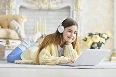 说谎在地板上和使用膝上型计算机的美丽的青少年的女孩 免版税库存图片
