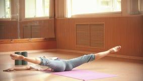 说谎在地板上和做在她的腿的年轻女人体操运动员锻炼-舒展 影视素材