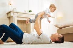 说谎在地板上和抱他的胳膊的快乐的父亲一个孩子 免版税图库摄影