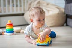 说谎在地板上在卧室和使用与玩具汽车的可爱的小孩男孩 库存图片