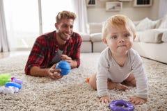 说谎在地板上的年轻父亲在家使用与小孩儿子 免版税库存照片