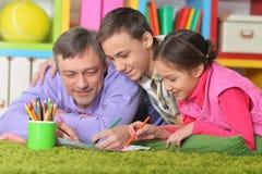 说谎在地板上的幸福家庭画象 免版税库存照片