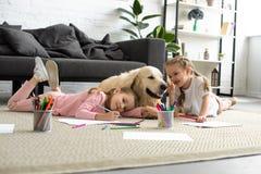说谎在地板上的微笑的孩子与金毛猎犬狗一起 免版税库存照片