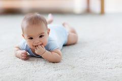 说谎在地板上的甜矮小的亚裔男婴 免版税图库摄影