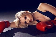 说谎在地板上的红色拳击手套的可爱的白肤金发的妇女 图库摄影