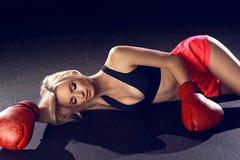 说谎在地板上的红色拳击手套的可爱的白肤金发的妇女 免版税库存图片