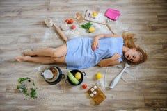 说谎在地板上的绝望主妇在她的厨房里 图库摄影