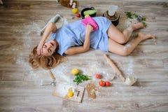 说谎在地板上的绝望主妇在她的厨房里 免版税图库摄影