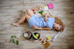 说谎在地板上的绝望主妇在她的厨房里 免版税库存照片