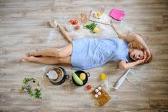 说谎在地板上的绝望主妇在她的厨房里 免版税库存图片