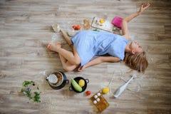 说谎在地板上的绝望主妇在她的厨房里 库存图片