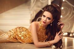 说谎在地板b上的金黄礼服的典雅的深色的性感的妇女 免版税库存图片
