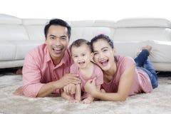 说谎在地毯的父母和孩子 图库摄影