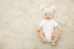 说谎在地毯背景的帽子和尿布的愉快的婴孩 免版税库存照片