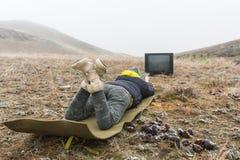 说谎在地面上和看老电视的自然的女孩 图库摄影