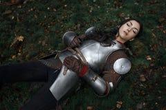 说谎在地面上的美丽的战士女孩佩带的chainmail和装甲在一个神奇森林里 免版税库存照片