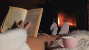 说谎在壁炉前面的一张软的地毯和读书的妇女 股票视频
