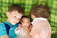 说谎在大家庭、拥抱和容忍的床上的三个兄弟姐妹孩子 免版税库存照片