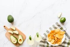 说谎在大理石背景的新鲜的鲕梨、石灰、饮料和烤干酪辣味玉米片芯片 Cinco de马约角党的食谱 顶视图,在头顶上,平展 库存图片