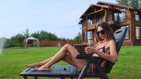 说谎在太阳懒人的泳装的一个美丽的浅黑肤色的男人在她与大Windows的别致的豪宅附近微笑并且挥动她 股票视频