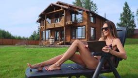 说谎在太阳懒人的泳装的一个美丽的浅黑肤色的男人在她与大Windows的别致的豪宅附近微笑,当工作时 影视素材