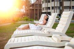 说谎在太阳懒人的白色礼服的美丽的年轻女人由海 旅行和夏天概念 免版税库存图片