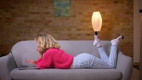 说谎在嬉戏地冲浪在膝上型计算机的沙发的胃的桃红色毛线衣的白肤金发的主妇在舒适家庭环境 股票录像
