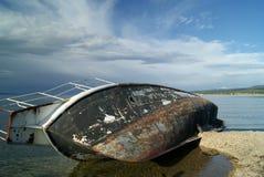 说谎在它的在岸的边的被放弃的船 库存照片