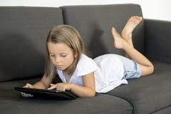说谎在家庭客厅沙发的年轻美好和愉快的小女孩6或7岁横卧使用互联网数字式片剂触摸板 免版税库存图片