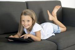 说谎在家庭客厅沙发的年轻美好和愉快的小女孩6或7岁横卧使用互联网数字式片剂触摸板 库存图片