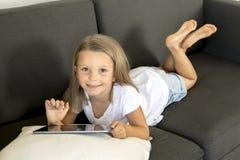 说谎在家庭客厅沙发的年轻美好和愉快的小女孩6或7岁横卧使用互联网数字式片剂触摸板 免版税图库摄影